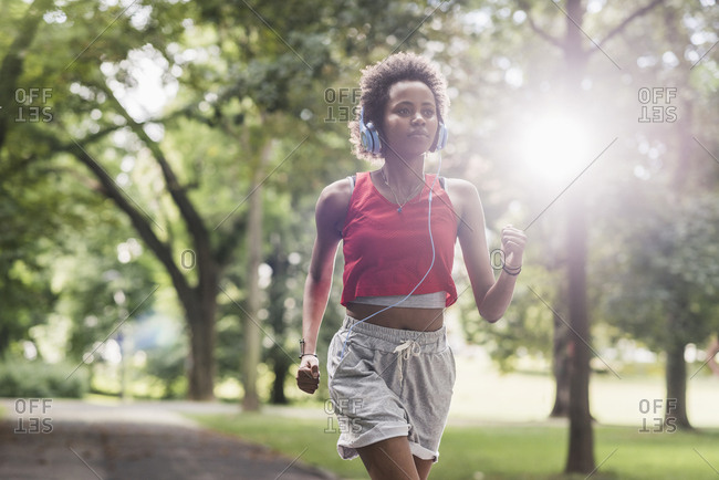 Young woman with headphones running in park