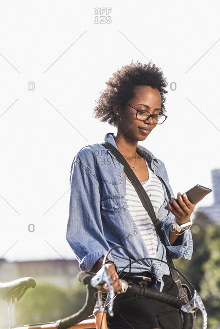 Young woman with cell phone pushing bicycle in park