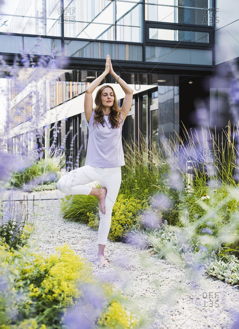 Woman practicing yoga in garden outside office building