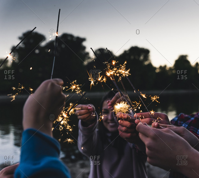 Group of friends at the riverside holding sparklers in the evening