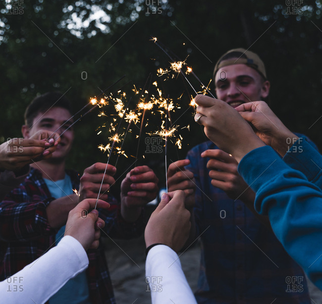 Group of friends holding sparklers in the evening