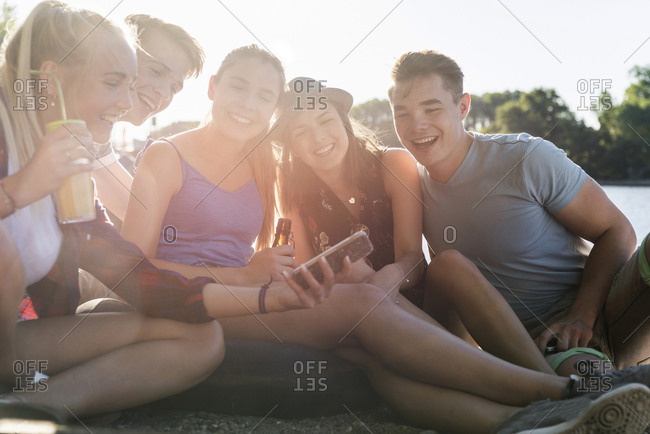 Group of happy friends sitting outdoors with drinks and cell phone