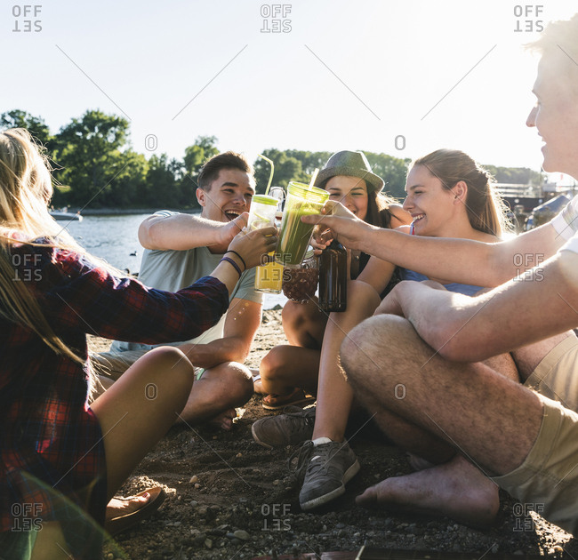 Group of happy friends sitting at the riverside toasting with drinks