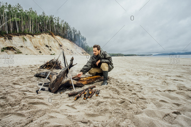 Man collecting firewood on the beach- preparing campfire