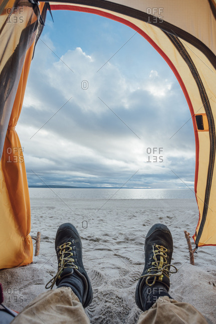 Feet of man- lying in tent on beach