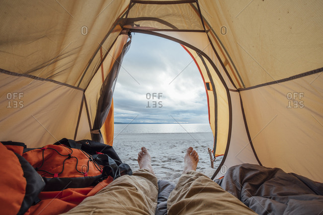 Feet of man- lying in tent on beach