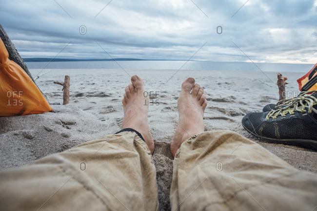 Feet of man- lying on the beach