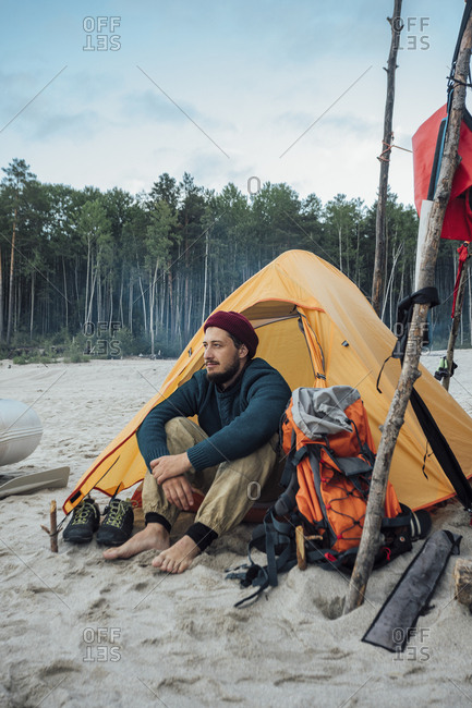 Backpacker sitting in front of his tent on the beach