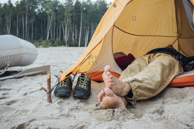 Man lying in tent on beach