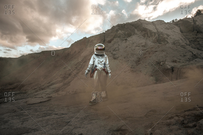 Spaceman exploring nameless planet- walking in a dust cloud