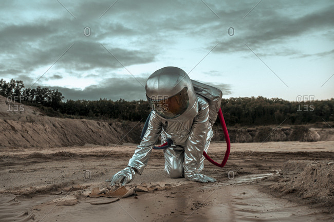 Spaceman exploring nameless planet- searching the soil