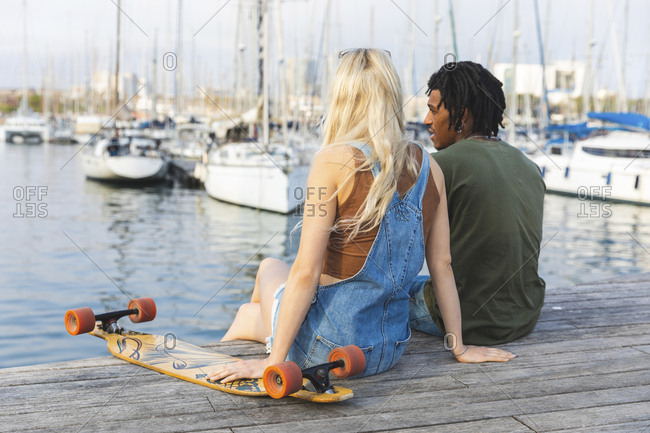 Spain- Barcelona- multicultural young couple with longboard relaxing at harbor