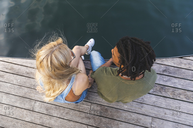 Multicultural young couple relaxing side by side on jetty- top view
