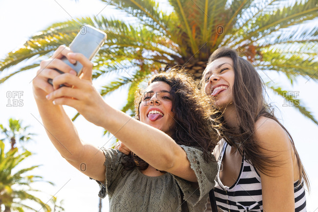 Two playful female friends taking a selfie under a palm tree