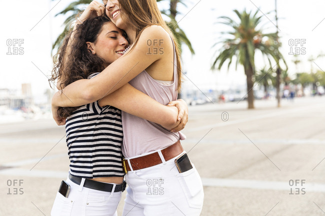 Two happy female friends embracing and hugging on promenade with palms