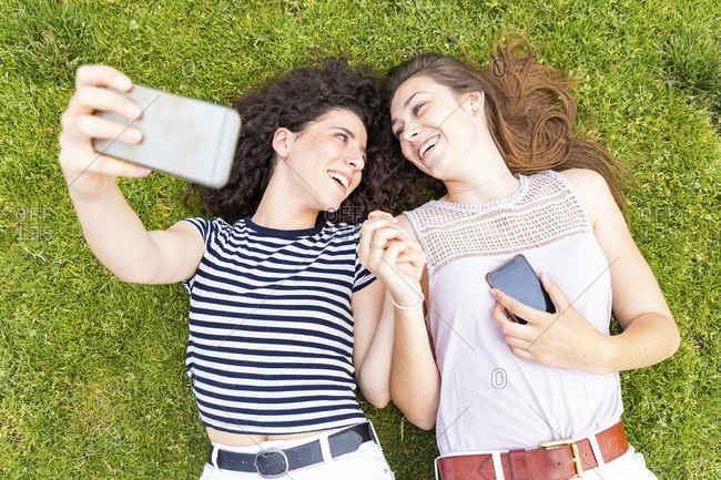 Two happy female friends lying down on grass taking a selfie