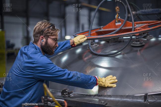 Worker in steel factory inspecting a tank