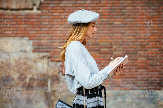 Chic woman wearing beret writing on notebook on the street.