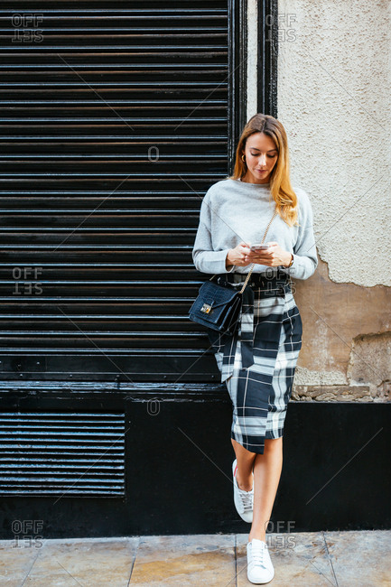 Chic young woman using phone on the street.