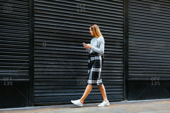 Chic young woman using phone walking on the street.