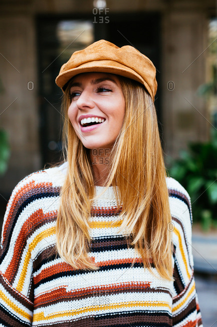 Portrait of a smiling chic woman wearing beret on the street.