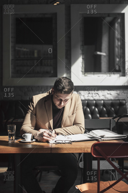 Handsome elegant Caucasian businessman sitting at cafe and writing in notebook.