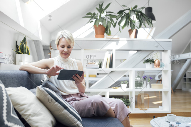 Pretty Caucasian woman sitting on couch at living room and enjoying reading magazine.