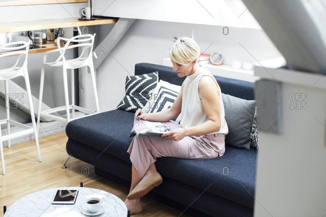Beautiful elegant blonde caucasian woman sitting in her living room an reading magazine.