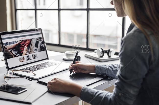 Cropped unrecognizable businesswoman designer working on pen tablet.