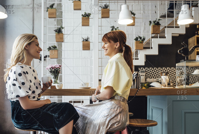 Two beautiful Caucasian women girlfriends sitting at coffee shop and smiling.