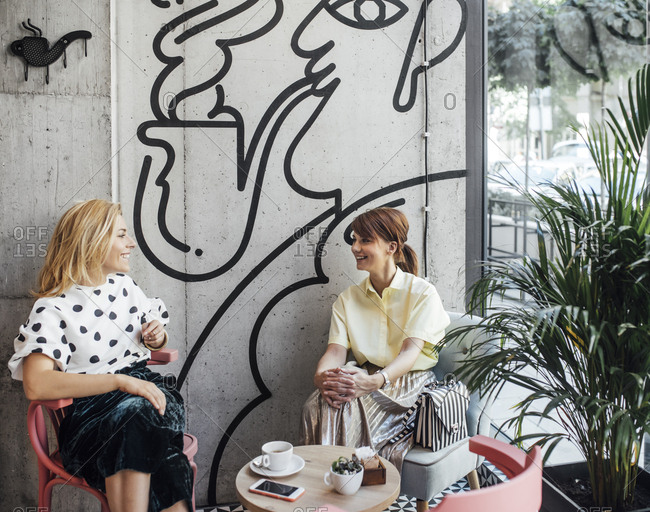 Two pretty Caucasian women girlfriends sitting at coffee shop and chatting.
