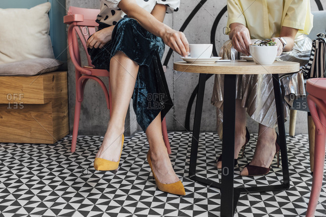 Two elegant stylish cropped unrecognizable Caucasian women drinking coffee at cafe.