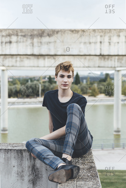 Portrait of young androgyne man seated in a fence  at urban park wearing checkered trousers