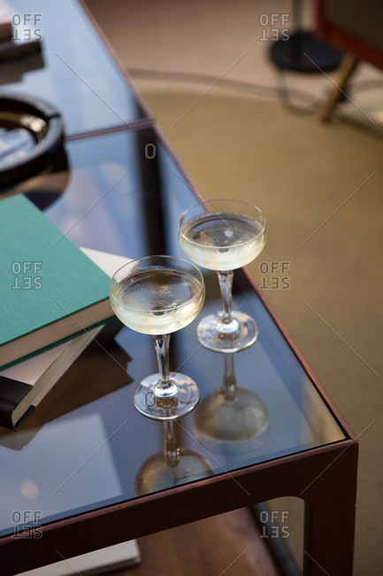 Two cocktails served on glass tabletop alongside books