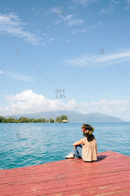Young woman wearing floral headband sitting on edge of wooden dock looking out over blue water in Tahiti