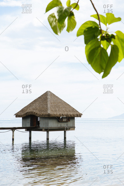 Thatched roof bungalow over water in Tahiti