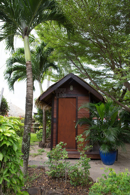 Small wooden building in tropical garden in Tahiti