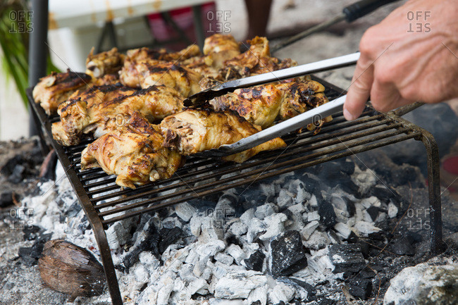 Person grilling chicken over hot coals