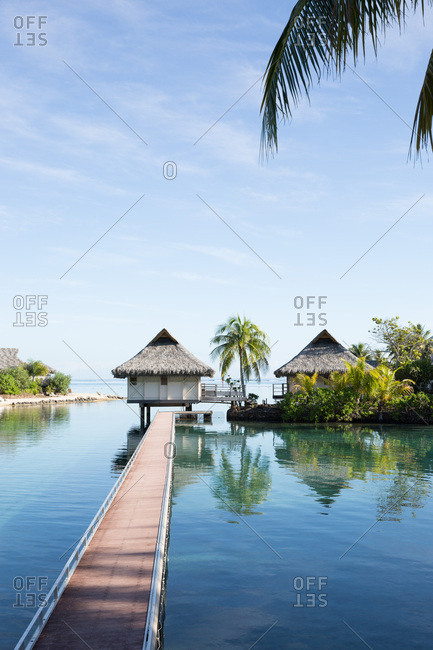 Overwater bungalows at end of long walkway over blue waters of lagoon on tropical island