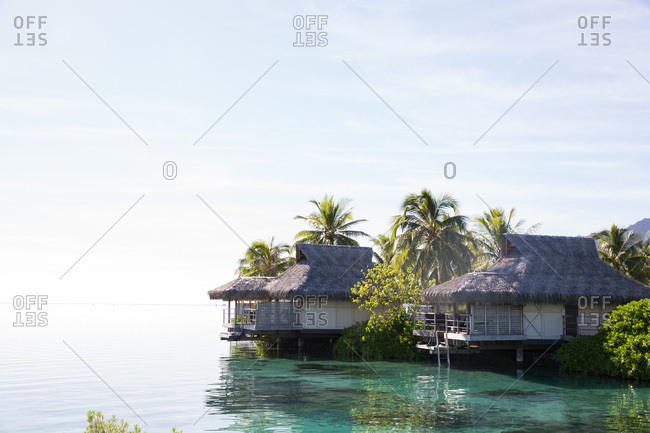 Overwater bungalows on tropical island lagoon