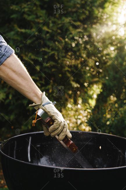 Man stirring coals in grill