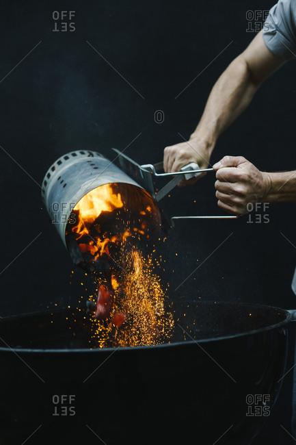 Man adding coals in grill