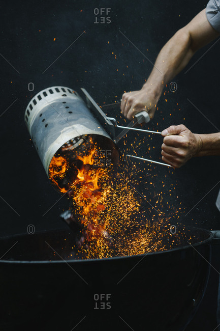 Man pouring coals into grill