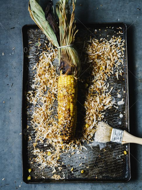 Overhead view of grilled corn on the cob and coconut