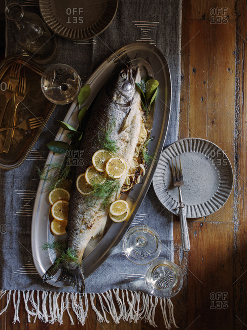 Platter of cooked fennel-orange stuffed whole roasted striped bass