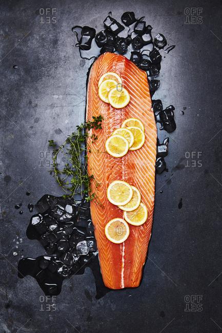 Fish fillet and lemon on dark background