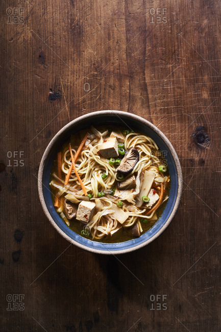 Shiitake and noodle hot and sour soup on wooden table