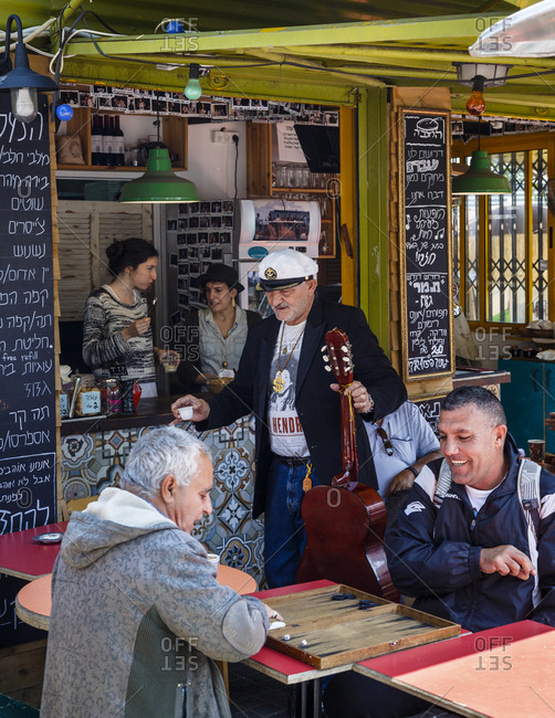 Jaffa, Israel - April 3, 2016: People playing backgammon at the Hamalabia Cafe in the flea market area