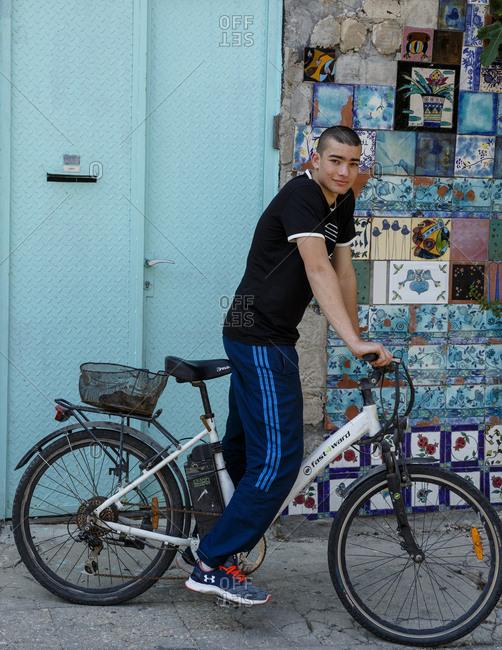 Jaffa, Israel - March 30, 2016: Portrait of young man riding bike on city street