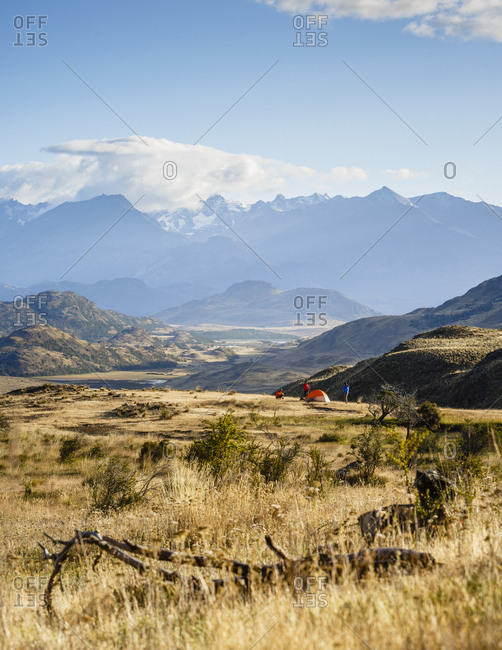 Hikers and camp at Chacabuco Valley with a view over the Jeinimeni Mountain peaks, Parque Patagonia, Aysen Region, Chile